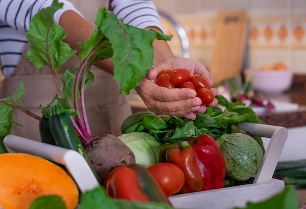 Mani di donna che tengono piccoli pomodori rossi mis di verdure fresche sul tavolo concetto vegetariano
