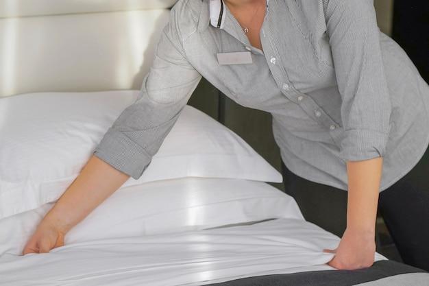 Mani della cameriera della donna che fa il letto nella camera d'albergo. governante che fa letto
