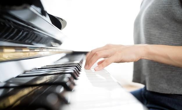 Mani di donna che suona il pianoforte