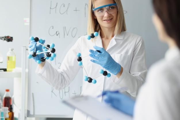 Nelle mani della donna lo scienziato tiene il modello molecolare nel concetto di ricerca del dna umano di laboratorio