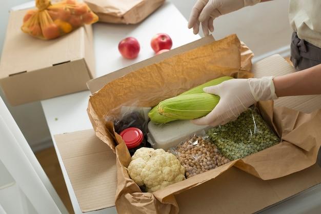 Le mani di una donna volontaria mettono il cibo in una scatola. consegna tramite corriere di generi alimentari.