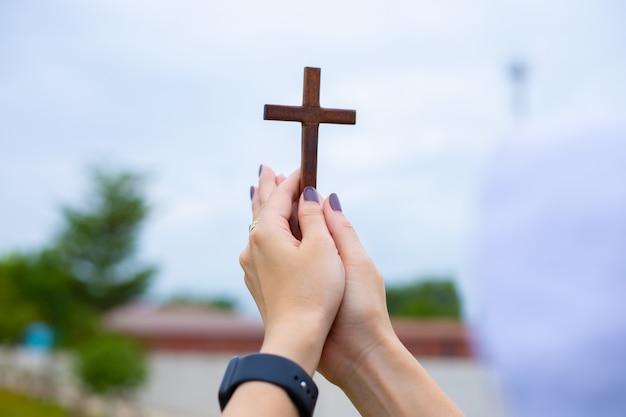 Mani di donna mentre pregano per la religione cristiana, donna casuale che prega con una croce, concetto di religione.