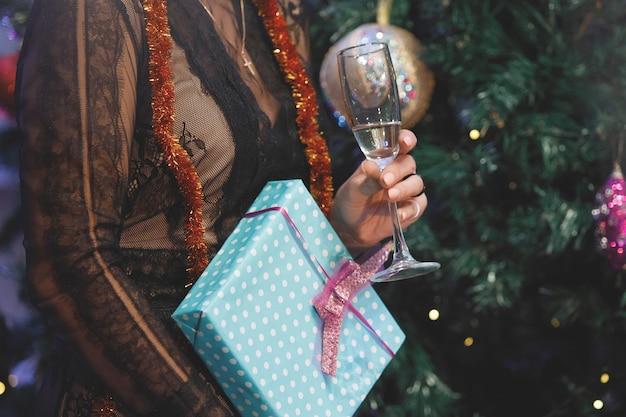 Mani di donna con una confezione regalo vicino a un albero di natale. filtro antirumore e grana speciale vintage, luci sfocate.