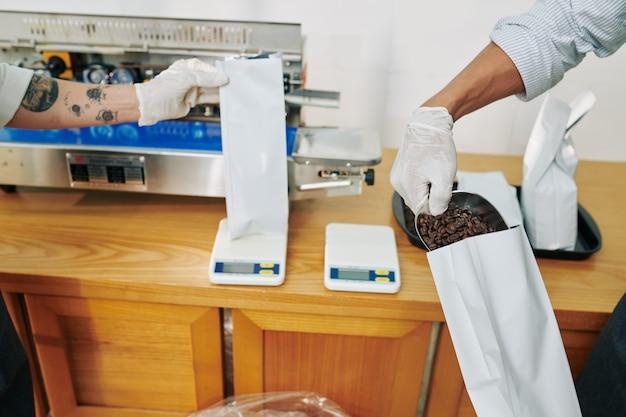 Mani dei lavoratori in guanti di gomma che ponderano e che imballano i chicchi di caffè per la vendita