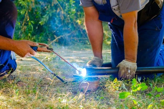 Mani dei lavoratori che saldano tubi metallici con saldatura ad arco elettrico. giornata di sole estivo.