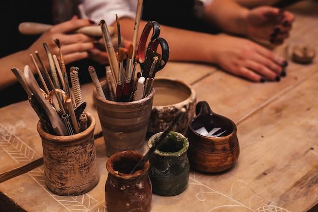 Mani che funzionano e che finiscono scultura con argilla sulla tavola di legno in officina