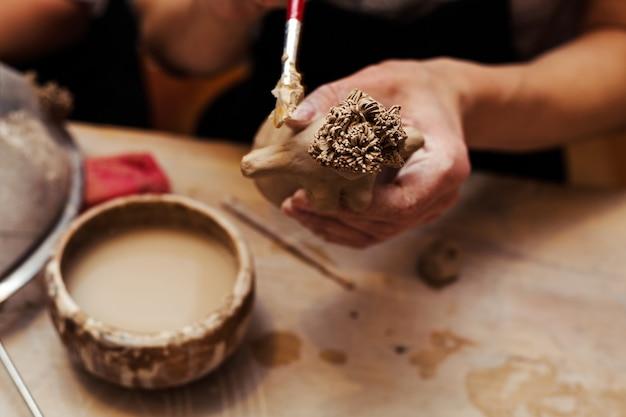 Mani che funzionano e che finiscono scultura con argilla sulla tavola di legno in officina Foto Premium
