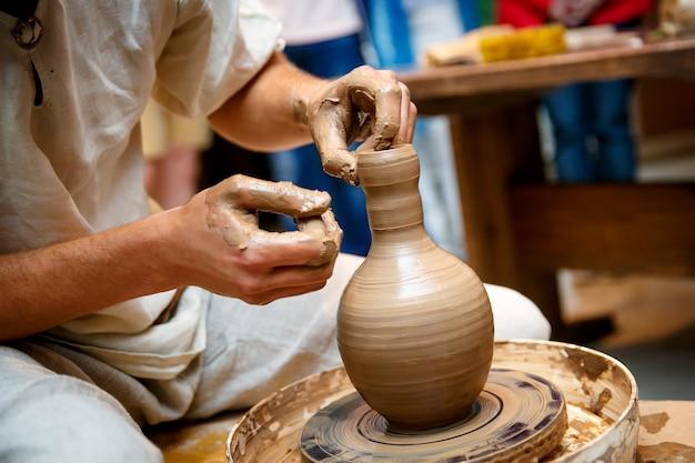 Mani che lavorano sul tornio, facendo un vaso