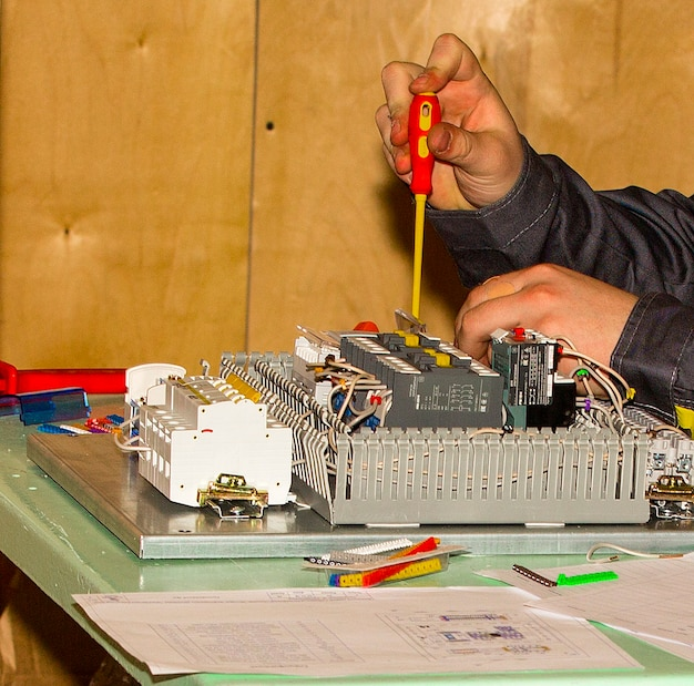 Le mani che lavorano avvitano la parte nel dispositivo di misurazione.