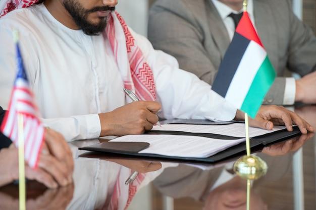 Mani di un giovane uomo d'affari arabo o delegato in abiti nazionali che firmano un contratto di partnership commerciale tra il suo paese e gli usa