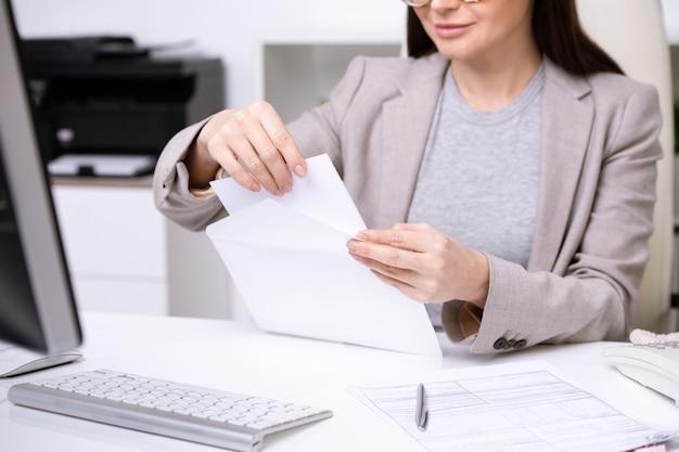Mani di giovane donna di affari o banchiere che mette carta piegata nella busta bianca prima di inviare il documento a uno dei clienti
