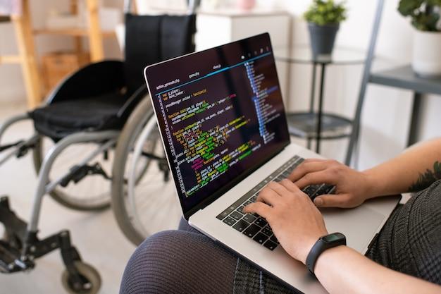 Mani di giovani contemporanei disabilitare programmatore femminile toccando i tasti della tastiera del computer portatile mentre si è seduti e si lavora in ambiente domestico