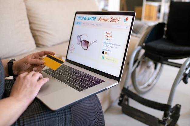 Mani di giovane donna disabile contemporanea che tiene la carta di credito sulla tastiera del laptop mentre va a fare ordine nel negozio online da casa