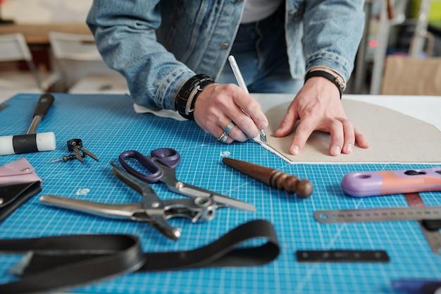 Mani del giovane artigiano chinarsi sul tavolo mentre delinea il cartamodello con la penna tra le forniture di lavoro