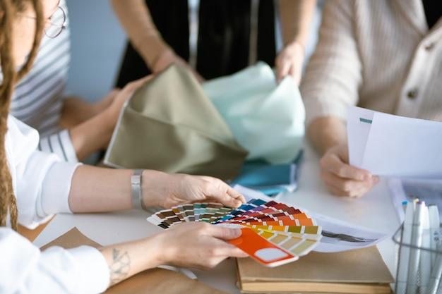 Mani del giovane designer che tiene la tavolozza dei colori sulla scrivania mentre si lavora con i colleghi sulla nuova collezione di moda