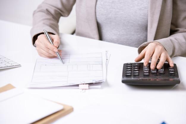 Mani del giovane ragioniere elegante con la penna sul documento finanziario premendo i pulsanti della calcolatrice mentre si lavora da scrivania