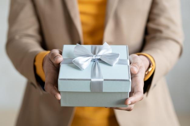 Mani di un giovane uomo d'affari elegante in abbigliamento casual intelligente che ti passa regalo confezionato in una confezione regalo blu chiaro con fiocco composto da un nastro di seta sulla parte superiore