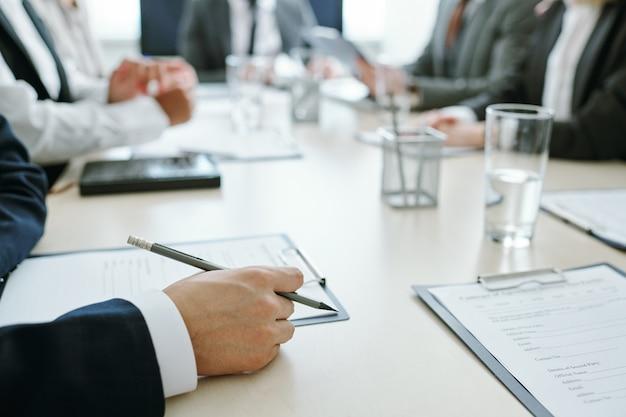 Mani di giovane uomo d'affari elegante in vestito che tiene matita negli appunti con contratto o altro documento con i colleghi