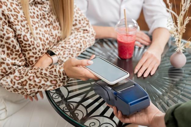 Mani di giovane donna elegante con smartphone tenendo gadget sul terminale di pagamento sul tavolo mentre si paga per le bevande nella caffetteria