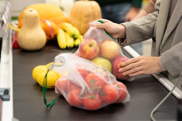 Mani di giovani consumatrici che mettono mele fresche e altri prodotti sul bancone mentre sono in piedi contro altri clienti nel supermercato
