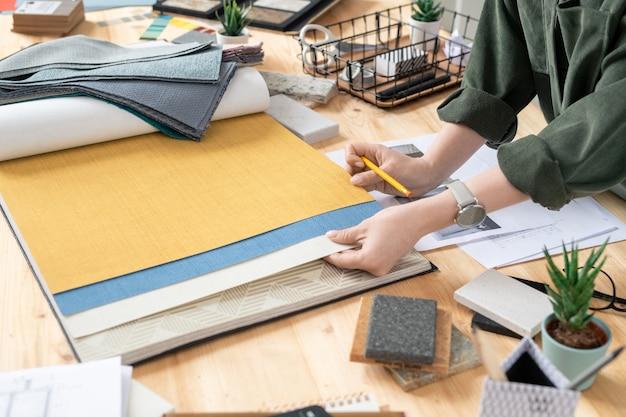 Mani di giovane designer creativo femminile di interni scegliendo sfondi