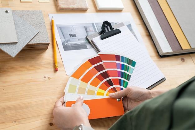 Mani di giovane donna designer di interni tenendo la tavolozza dei colori sulla scrivania mentre si sceglie quella adatta per il nuovo ordine del cliente
