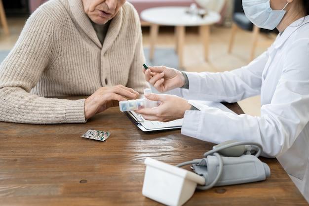 Mani della giovane dottoressa in camice bianco e maschera protettiva che passano il contenitore con le pillole a un uomo anziano malato mentre gliele prescrivono