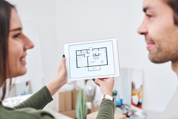 Mani di giovane donna che tiene compressa digitale con piano di appartamento mentre guarda il marito durante la discussione del documento