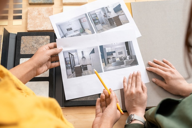 Mani di giovani designer di interni femminili che guardano attraverso le fotografie di stanze moderne mentre discutono del loro stile e scelgono uno di loro