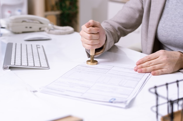 Mani di giovane impiegato femminile seduto alla scrivania e mettendo il sigillo sul documento finanziario prima di inviarlo al cliente