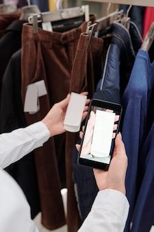 Mani di giovane assistente di negozio femminile con lo smartphone che cattura foto del prezzo sull'etichetta mentre guarda attraverso la nuova collezione