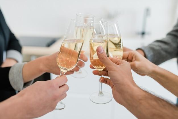 Mani di giovani amici che tengono flauti di spumante di champagne e tintinnano con loro mentre fanno brindisi per le vacanze alla festa