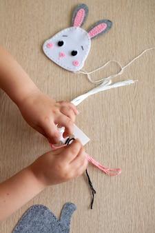 Mani di un primo piano di giovane ragazza, lei cuce un giocattolo di macramè dal filo.