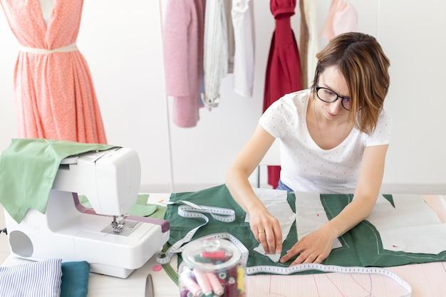 Le mani di una giovane designer di ragazza fanno segni per un nuovo prodotto di cucito seduto al tavolo accanto alla macchina da cucire. concetto di business creativo e design