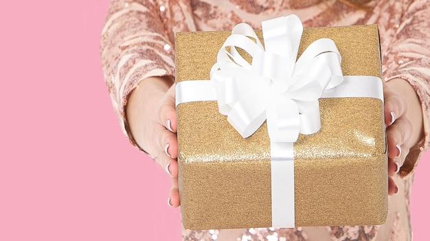Le mani di una giovane ragazza in un abito festivo dorato tengono e danno una scatola d'oro con un regalo in un nastro bianco.
