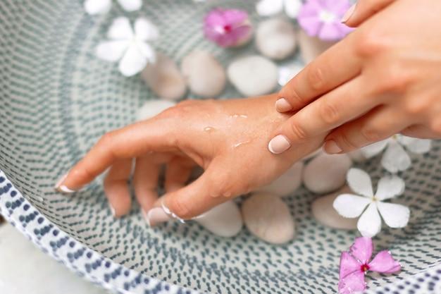 Mani di giovane ragazza con manicure naturale sulle unghie e ciotola con acqua e fiore. trattamenti termali e massaggi per mani femminili.