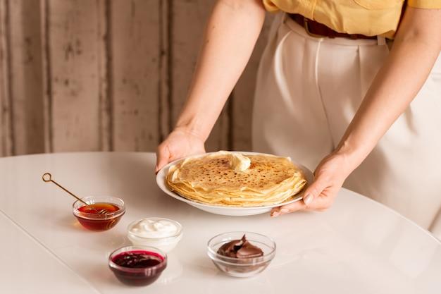 Mani della giovane casalinga mettendo la piastra con la pila di frittelle calde fatte in casa sul tavolo con miele, panna acida, marmellata e cioccolato
