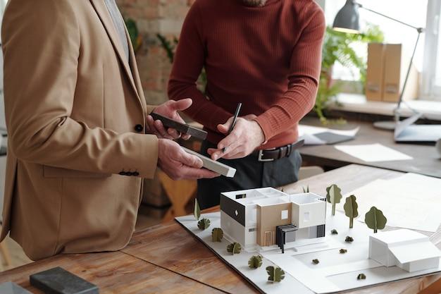 Mani di un giovane architetto maschio con una matita che punta a uno dei blocchi tenuti dal suo collega maturo per il modello della nuova casa e del cortile