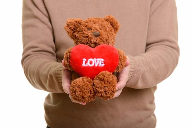 Mani di giovane uomo dando orsacchiotto pronto per il giorno di san valentino
