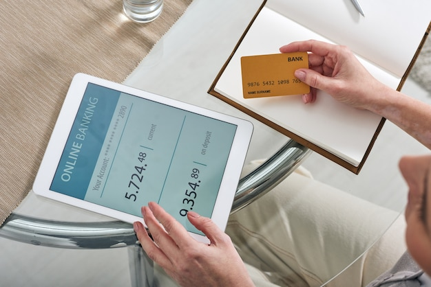 Mani di giovane donna mobile con carta di credito e touchpad seduti a tavola mentre guarda attraverso il suo conto bancario online
