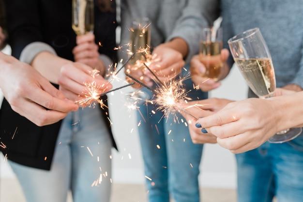 Mani di giovani amici multiculturali che tengono le luci brucianti del bengala e flauti di champagne alla festa di capodanno