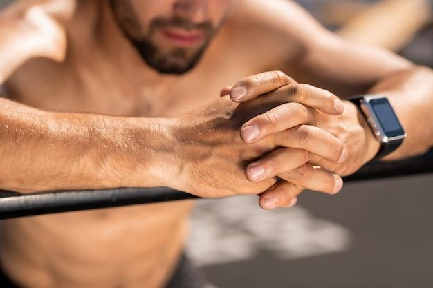Mani del giovane atleta senza camicia sopra lo sportsbar durante l'allenamento o il riposo dopo l'allenamento all'aperto