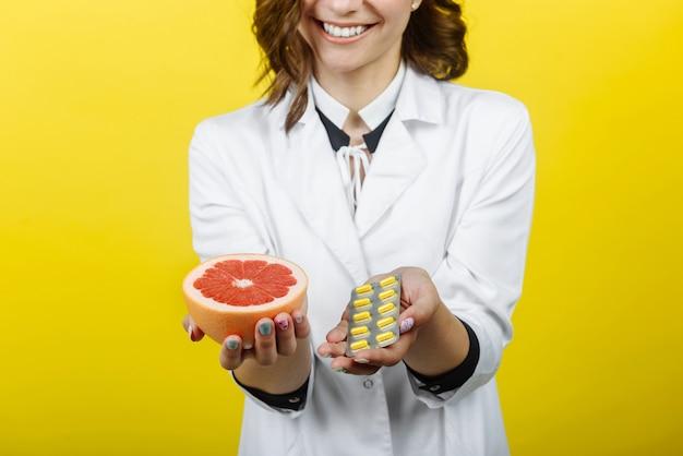 Mani il giovane medico sorridente nutrizionista donna tiene un pompelmo fresco e un piatto di compresse con vitamina c e li confronta.