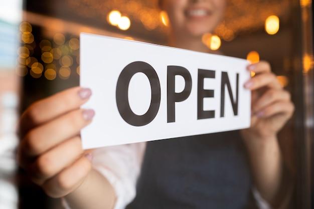 Mani del giovane cameriere o proprietario del ristorante o del bar che mettono avviso aperto sulla porta all'inizio della giornata lavorativa