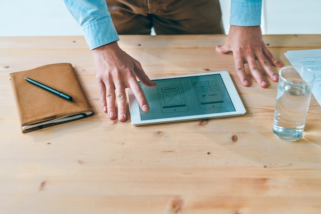 Mani del giovane progettista di siti web sulla progettazione del programma sul display del touchpad sul tavolo di legno durante il lavoro