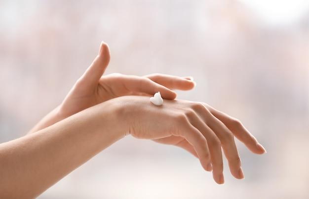 Mani della giovane donna che applica la crema a casa
