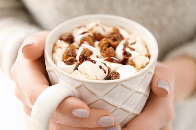 Mani della giovane donna e tazza di gustosa bevanda al cacao, primo piano