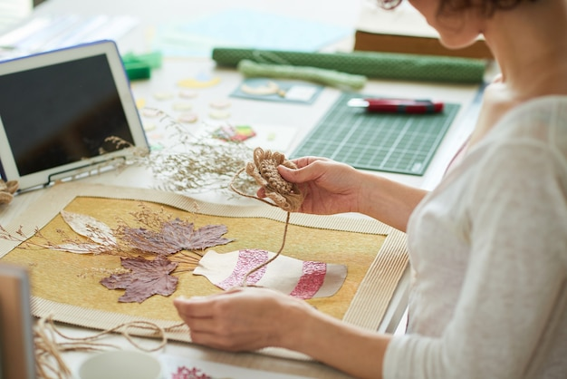 Mani di una giovane donna che seguono un tutorial sul tablet quando si lavora su opere d'arte in stile oshibana