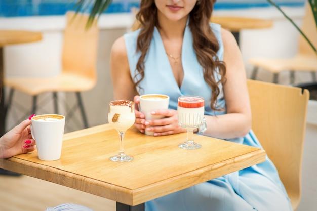 Mani di una giovane donna che tiene una tazza di caffè con diversi cocktail sul tavolo del bar
