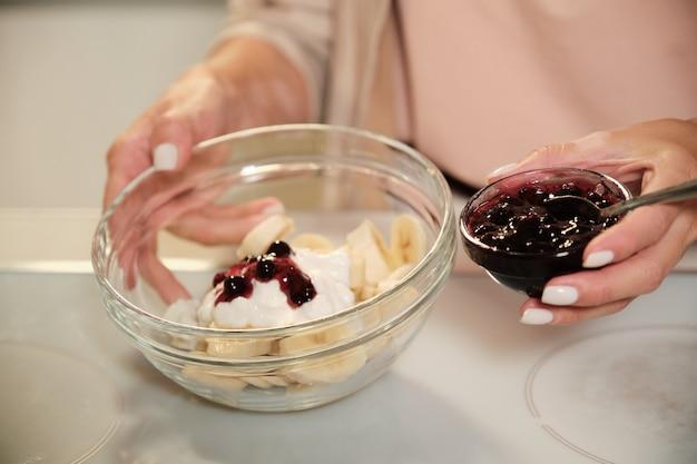 Mani della giovane donna che tiene una piccola ciotola con marmellata di ribes nero e una più grande con ingredienti di gelato fatto in casa sul tavolo